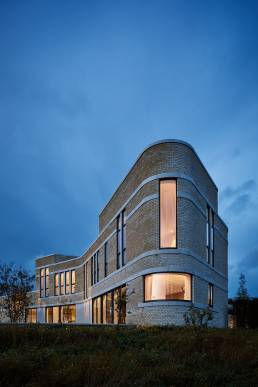 A house in the Cotswolds designed by Adrian James Architects at dusk
