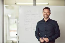 Business portrait of man at white board