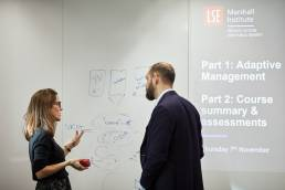 A teacher with student of the Marshall Institute in front of a white board at the London School of Economics
