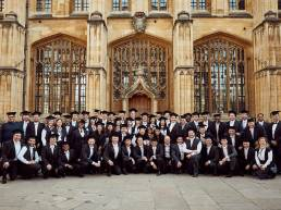 A large group of University of Oxford students in front of the Divinity School