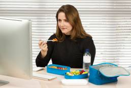 Woman eating lunch from blue lunch box at her desk