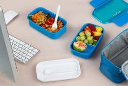 Blue lunchbox with food in front of computer