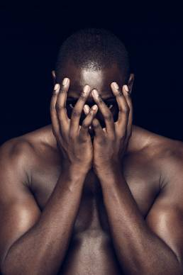 Black man with hands over face against dark background in the studio