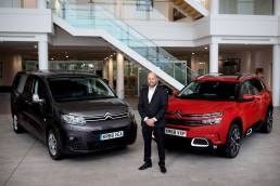 Businessman in suit standing between two Citroen cars in Coventry