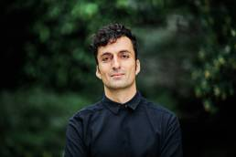 Outdoor headshot of man in black against natural dark background