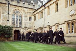 Large group of choir singers walking in Oxford quad