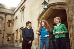 University of Oxford student helper with visitors in quad