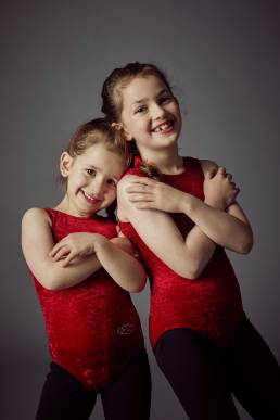 Studio photograph of two sisters in red leotards