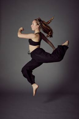 Studio dance photo of girl in hareem pants leaping
