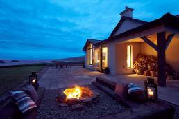 Outdoor scene of cottage with fireplace at dusk