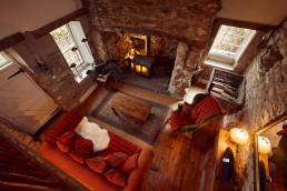 Aerial view of cottage living room with fire