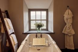 Bath tub in cottage with bathrobe and book