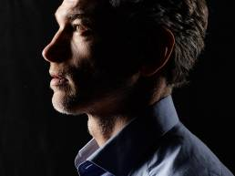 Profile of man in studio with black background