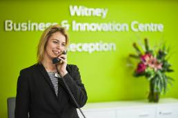 Receptionist on telephone at Witney Business and Innovation Centre in Oxfordshire