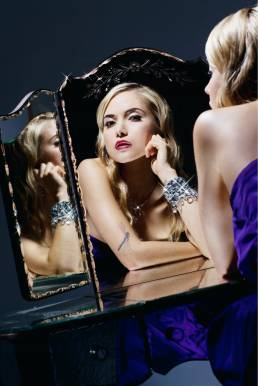 Woman at makeup mirror with sparkling jewel bracelet under studio lighting