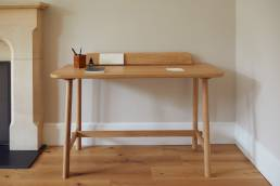 Wooden desk designed by Alexander Hay by fireplace