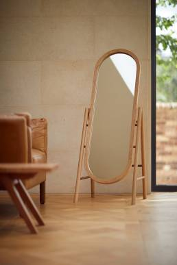 Wooden mirror designed by Alexander Hay in living room