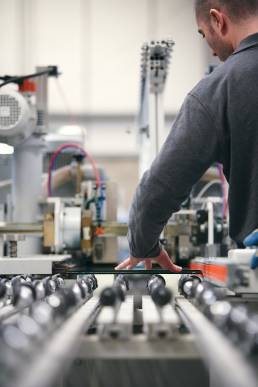 Man in factory with a piece of glass on a production line