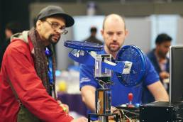 A delegate and a National Instruments team member looking at a demonstration at NI Days in London