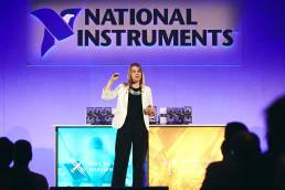 Engineer on stage addressing audience in front of National Instruments logo