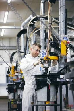 Worker in plastics factory using industrial equipment